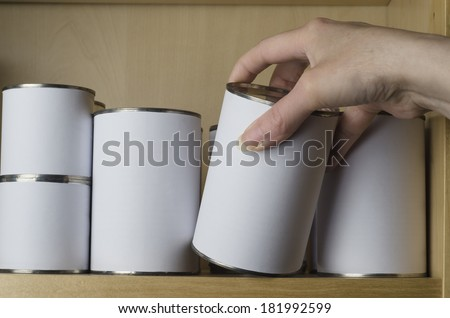 A selection of tin cans in various sizes on a shelf, with female hand reaching in from the right to select one.  Labels are unbranded and blank white for copy space. - stock photo