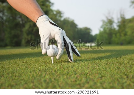 A selective focus, low angle view of a golfer's gloved hand placing a ball on a tee - stock photo