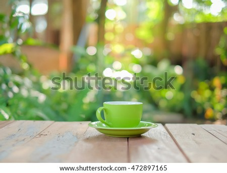 a selective focus picture of a cup of coffee on wooden table in green garden