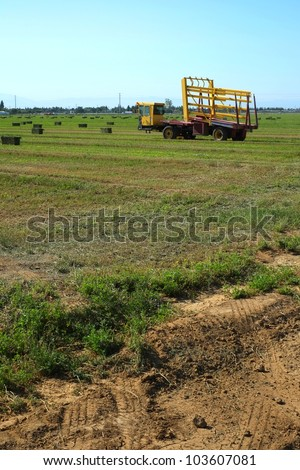 A self-propelled wagon gathers up hay bales in a California alfalfa field - stock photo