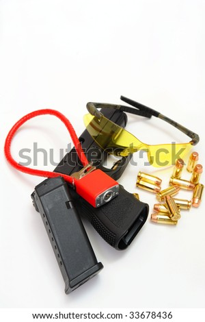 A semi automatic pistol with a 10 round magazine, brass cartridges, amber colored protective eye ware and a cable lock to secure the weapon when not in use. - stock photo