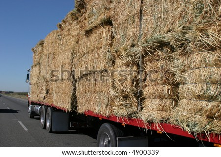 a semi truck hauling hay bails barrels down interstate 5 in northern california - stock photo