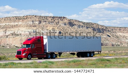 A semi-truck on the road in the desert - stock photo