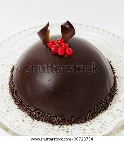 a semispherical chocolate cake with a cranberry twig on top - stock photo