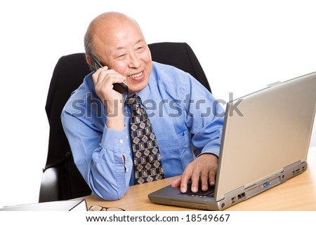 A senior asian businessman talking on the phone while working on his laptop - stock photo