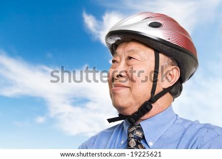 A senior asian businessman wearing a bike helmet outdoor - stock photo