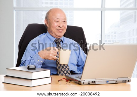 A senior asian businessman working in the office - stock photo