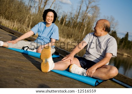 A senior asian couple stretching before exercise