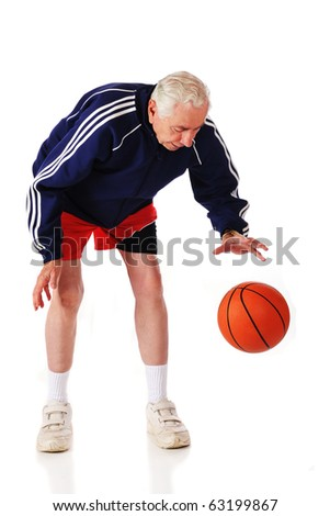 A senior athlete in sportswear dribbling a basketball.  Isolated on white.  Some motion blur on ball and dribbling hand. - stock photo