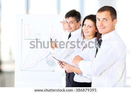 A senior business executive delivering a presentation to his colleagues during a meeting or in-house business training - stock photo