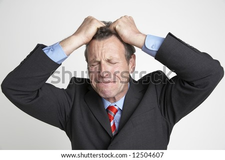A senior businessman tears his hair out in desperation - stock photo