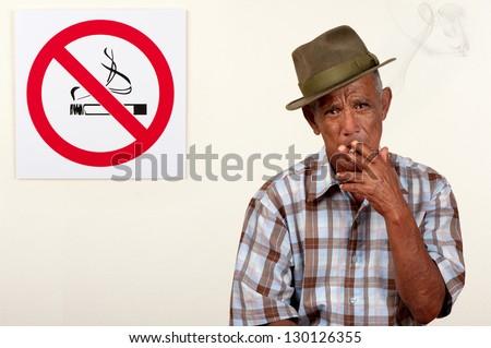 A senior citizen pays scant regard to a non-smoking sign. - stock photo