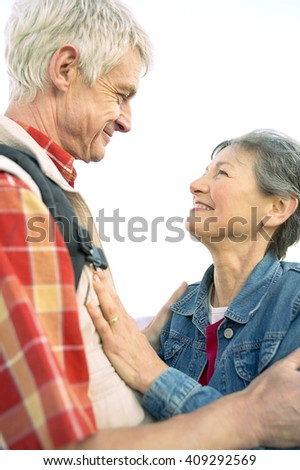 A senior couple, close together, looking at each other - stock photo