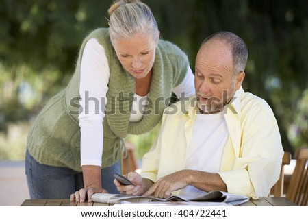 A senior couple discussing an article in a paper