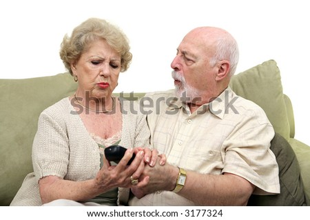 A senior couple fighting over the television remote control.  White background. - stock photo