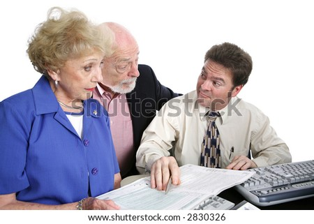 A senior couple going over their taxes with a shady accountant.  He has just suggested something sneaky.  Isolated on white. - stock photo