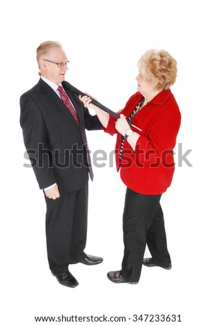 A senior couple he in a suit and she in a red jacked holding the handle ofa umbrella around the mans neck, isolated for white background. - stock photo