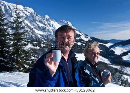 A senior couple in a winter setting in the alpine mountains. Active and happy seniors.They are having a cup of tea. - stock photo