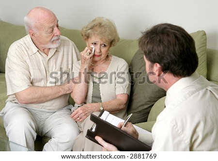 A senior couple in counseling - either grief counseling or marriage counseling.  The wife is crying and the husband is wiping her tears and trying to console her. - stock photo