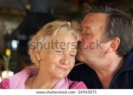 A senior couple is kissing and cuddling. - stock photo