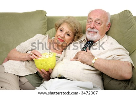 A senior couple relaxing and watching television together on the couch. - stock photo