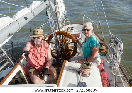 A senior couple sail on their classic ketch as he points to indications of wind on the water ahead while she steadies the helm. - stock photo