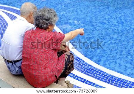 a senior couple sitting beside a pool - stock photo