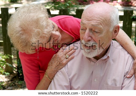 A senior couple.  The wife is caring for the husband. - stock photo