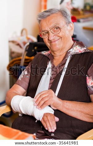 A senior, elderly woman, with broken, but treated arms, sitting at the table, smiling at the camera.