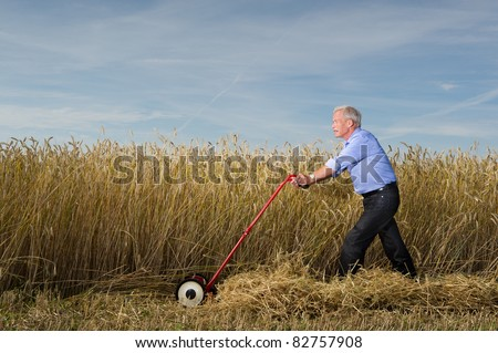 A senior executive businessman strides through a field of ripe grain pushing a manual lawnmower as he harvests and reaps the rewards of all his hard work and business planning - stock photo