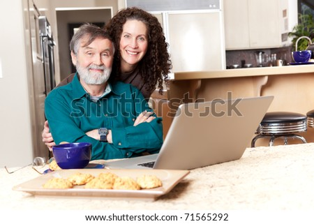 A senior father with his middle age daughter using a laptop - stock photo