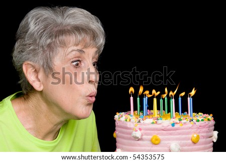 A senior female blows out candles on a cake.  Ideal for birthday, anniversary or any other celebration inference. - stock photo
