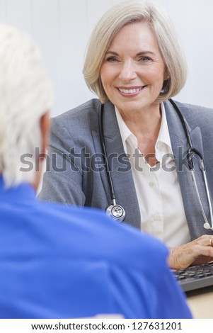 A senior female woman doctor sitting at a desk wearing a suit and stethoscope talking to an elderly male patient - stock photo