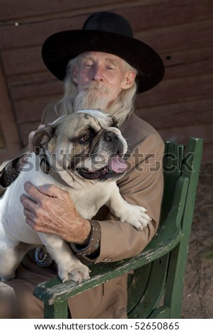 A senior gentleman wearing a western style suit and cowboy hat is sitting in a chair with a bulldog. Vertical shot. - stock photo
