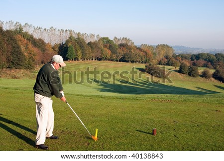 A senior golfer teeing off with a driver on a golf course in England in early autumn. Photo taken at point of contact, with motion blur on the golf ball. - stock photo