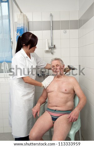 a senior is bathed by nurses - stock photo