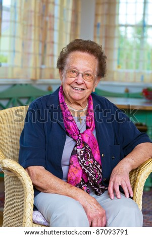 a senior is sitting in a chair and looking forward. - stock photo