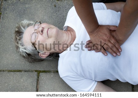 A senior lade with cardiac arrest or stroke receiving cpr - stock photo