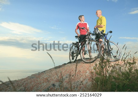 A senior man and a woman on bike at the sunset. - stock photo