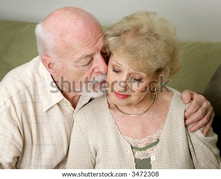A senior man and wife deeply in love.  She is upset and he is comforting her. - stock photo