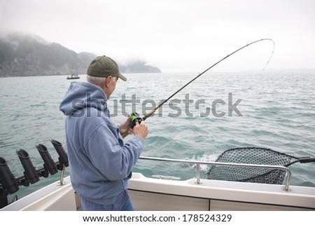 A senior man catches a salmon while fishing in Alaska - stock photo