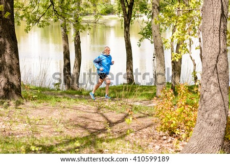 A senior man dressed in black and blue is running close to the lake during a warm spring day