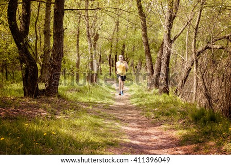 A senior man dressed in black and yellow is running in the forest, during a warm spring day evening