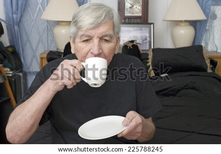 A senior man drinking from a coffee cup at home. - stock photo