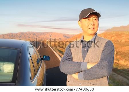 A senior man drives in the desert - stock photo