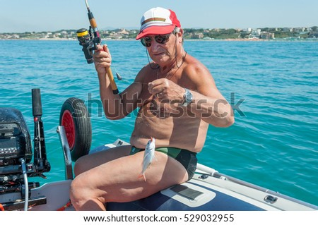 A senior man enjoy fishing on a boat in the mediterranean sea in Italy