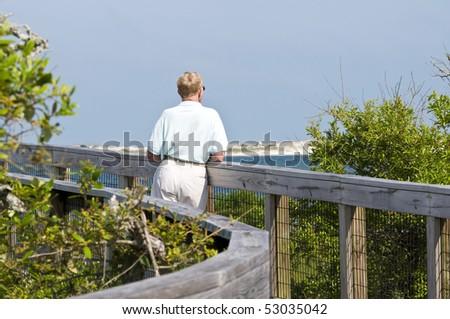 A senior man enjoying nature alone. - stock photo