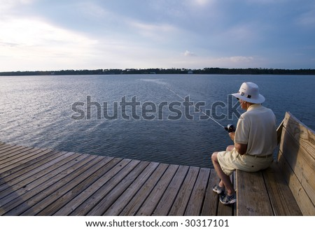 A senior man fishing alone from the pier.