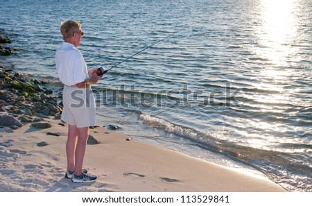 A senior man fishing from the beach on the gulf coast.