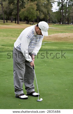 A senior man golfing on a spring vacation in Florida. - stock photo